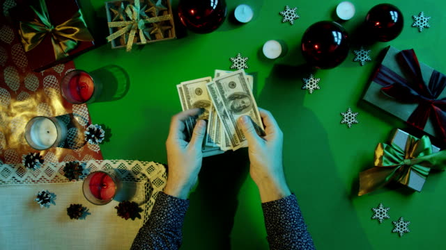 Top down shot of man counting cash money by New Year table with chroma key video
