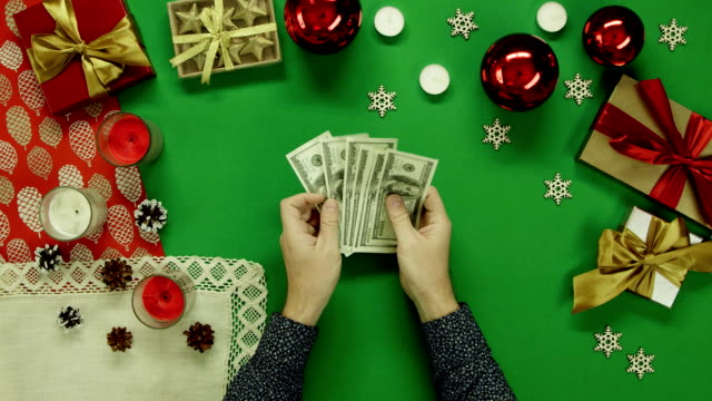Top down shot of man counting cash money by Xmas table with chroma key video