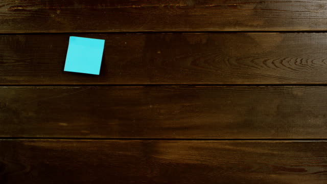 top down shot of man hands sticking the notes on wooden desk - post it video stock e b–roll