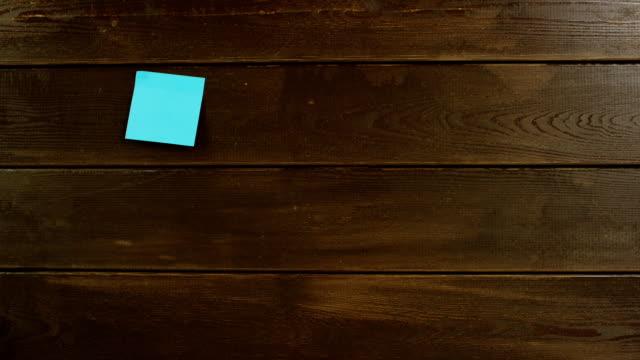 トップダウンの木製の机の上のノートをこだわり男の手のショット ビデオ