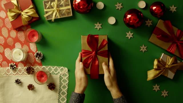 上下にクロマ キーを持つテーブルで本物の人間の心のクリスマス ギフト ボックスを開く男のショット ビデオ