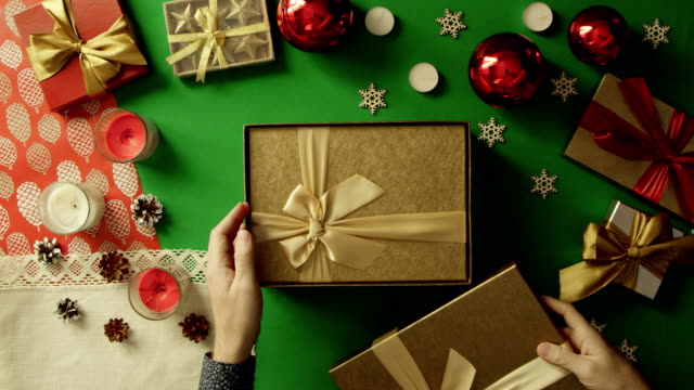 Top down shot of man opening Christmas gift box with sticky note with smile on it inside on table with chroma key video