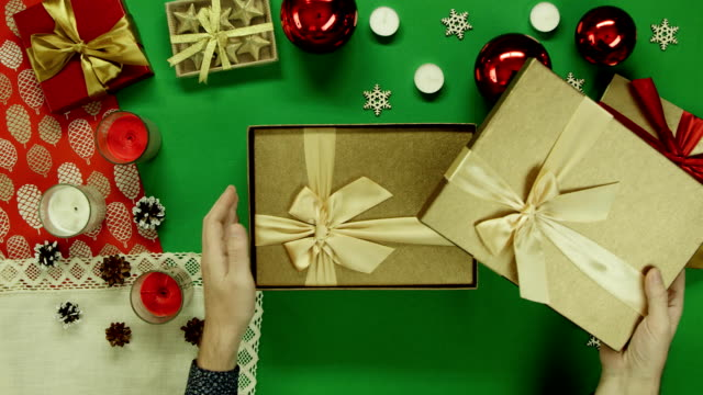 Top down shot of man opening Christmas present box with only a sticky note with smile on it inside on table with chroma key video
