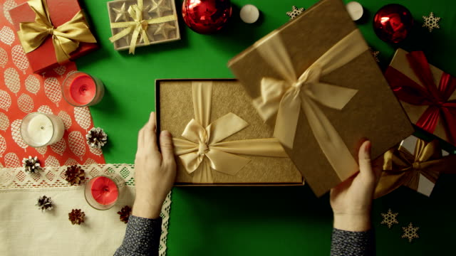 Top down shot of man opening empty Christmas gift box by table with chroma key video
