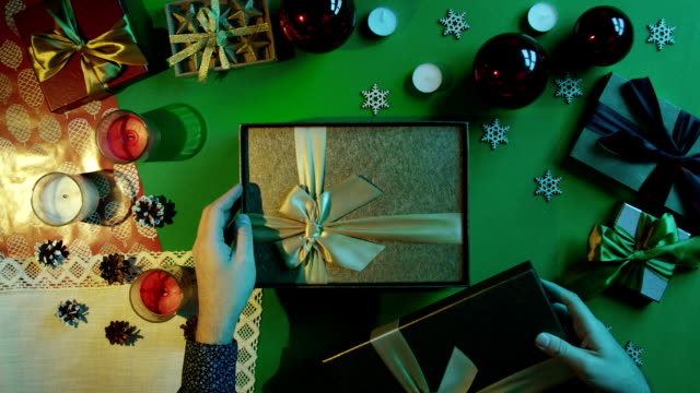 Top down shot of man opening empty New Year gift box by table with chroma key video
