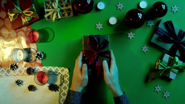 上下にクロマキーとテーブルの上の本物の人間心で新年のギフト ボックスを開く男のショット ビデオ