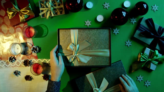 Top down shot of man opening New Year gift box with sticky note with smile on it inside on table with chroma key video