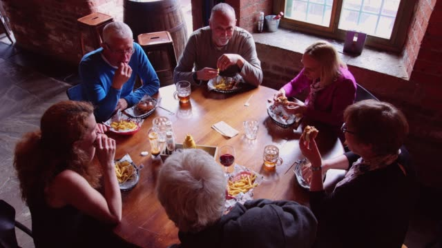top down shot of mixed age group of people enjoying beer and burgers in a pub - baby boomers stock videos & royalty-free footage