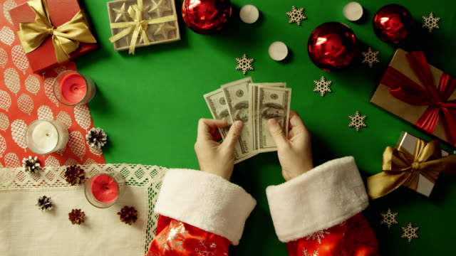 Top down shot of Santa Claus counting cash money by Christmas table with chroma key video