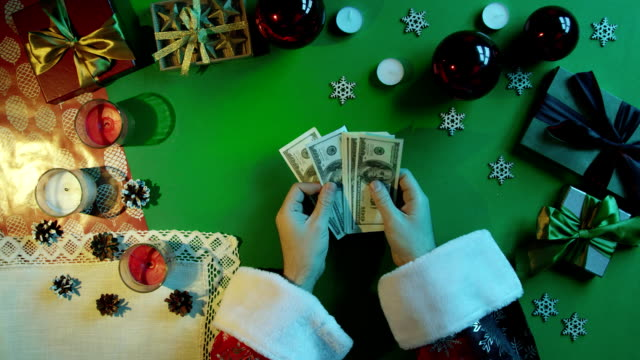Top down shot of Santa Claus counting cash money by New Year table with chroma key video