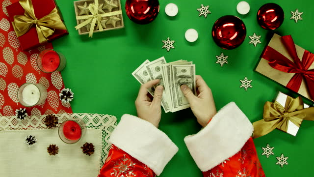 Top down shot of Santa Claus counting cash money by Xmas table with chroma key video