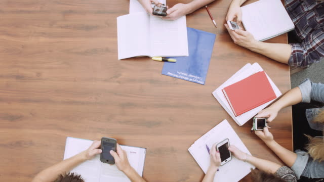 Top down shot of university students using their cell phones at a large table video