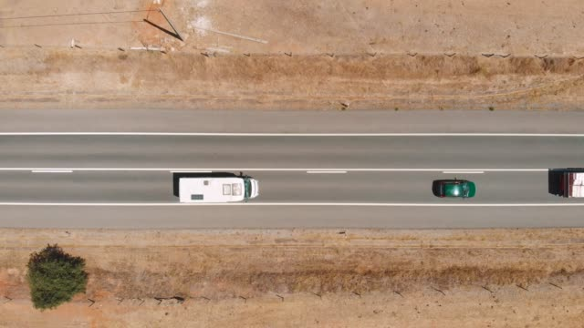 vídeos de stock e filmes b-roll de top down view flying over desert road with trucks - mapa portugal