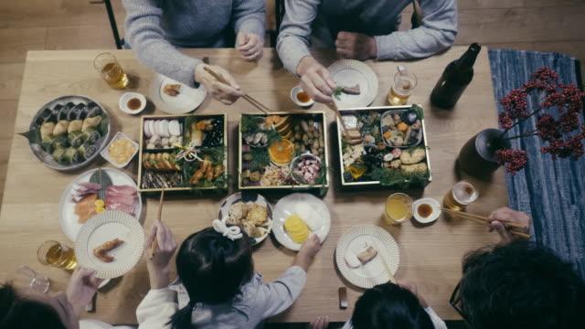 大晦日にオセチリョリを食べる日本人家族のトップダウンビュー - テーブル点の映像素材/bロール