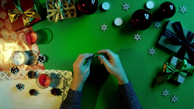 Top down view of man unwrapping candy and throwing wrapper on New Year decorated table with chroma key video
