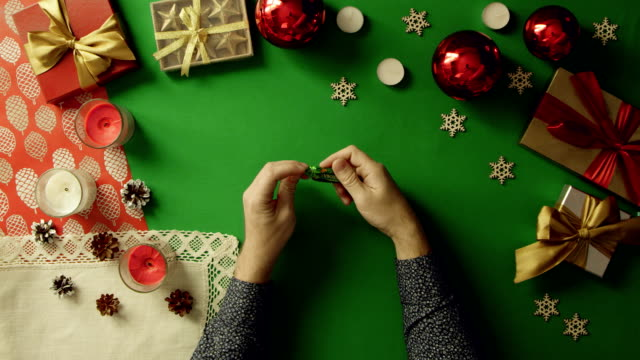 Top down view of man unwrapping candy and throwing wrapper on Christmas decorated table with chroma key video