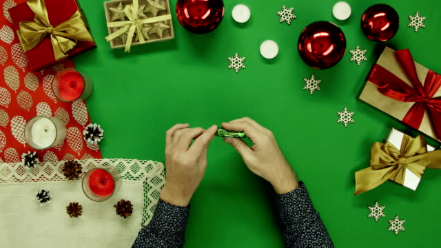 Top down view of man unwrapping candy and throwing wrapper on Xmas decorated table with chroma key video