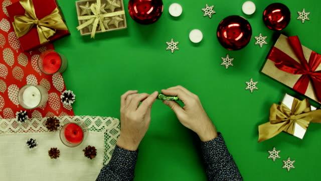 クリスマスに観男アンラップ キャンディと投げラッパー トップダウンは飾らクロマ キー テーブル ビデオ