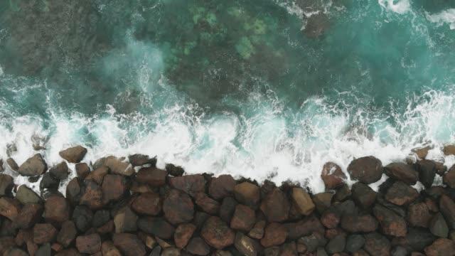 yukarıdan aşağıya görünüm. bir kuş bakışı görünümü-okyanus sahili güçlendirmek ve korumak için taşlar yapımı. büyük taşlar ve turkuaz renk okyanusu. - dalgakıran stok videoları ve detay görüntü çekimi