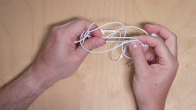 vídeos y material grabado en eventos de stock de arriba hacia abajo vista desenredando auriculares - cable