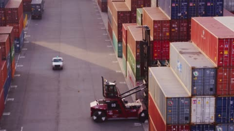 Top Handler Arranging Containers in Yard at Port of Long Beach - Aerial View View of an intermodal shipping yard in the Port of Long Beach, California.View of an intermodal shipping yard in the Port of Long Beach, California. The drone pulls back, away from a top handler among the rows and rows of containers as it unloads a UTR. container stock videos & royalty-free footage