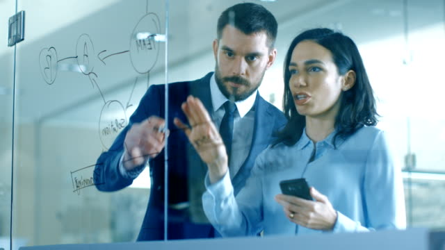 vídeos de stock e filmes b-roll de top manager and female executive outlining company optimization plan on a glass blackboard, drawing with market and using smartphone while standing in the modern glass and concrete office. - novo