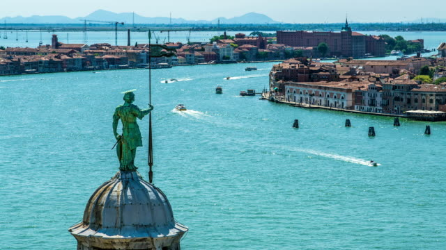Top of belfry with Saint George statue in Venice, traffic on Grand Canal, travel video