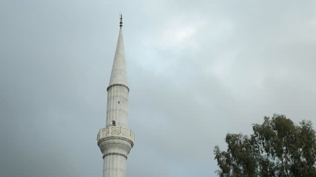 Top of mosque against grey cloudy sky. Muslim culture and religion. Islamic symbols