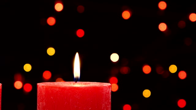 Top of two red candles with christmas decorations on black, bokeh, light, garland video