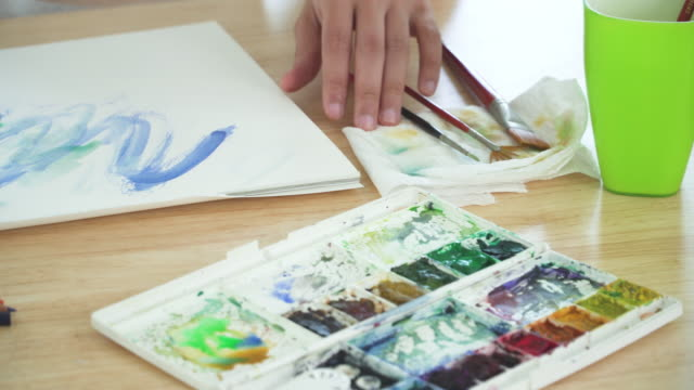 Top panning view: watercolor equipment such as paintbrush and part of Asian handsome man painting one paper page with watercolor to create artist skill and imagination. Concept of young adult and leisure activity at the weekend.