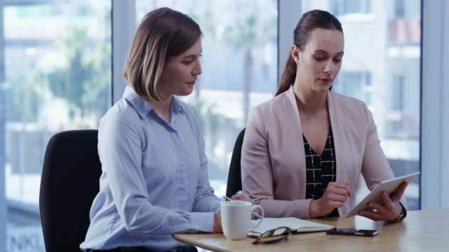 Top performers use top performing apps 4k video footage of two young businesswomen using a digital tablet in a modern office employee engagement stock videos & royalty-free footage