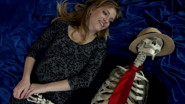 Top shot of smiling female holding skeletons hand Top view of a strange pair laying on a bed smiling and touching boyfriend stock videos & royalty-free footage