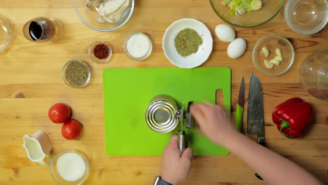 Top view. A man opens a tin of beans in the kitchen before dinner video