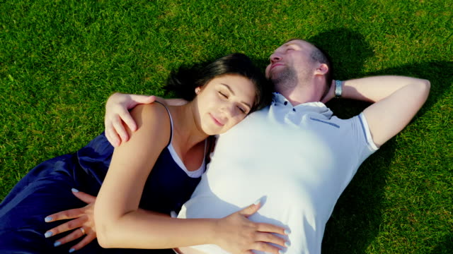 Top view: A man with a pregnant wife is lying on the green grass video