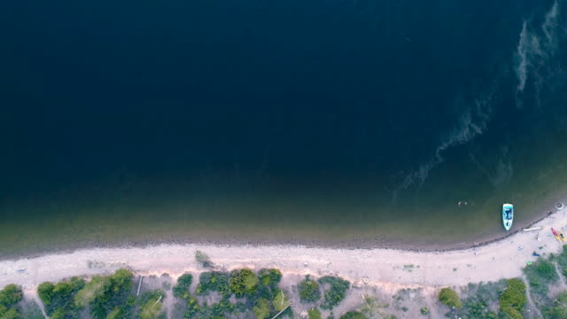 Top view aerial of mountain lake to white sandy shore video