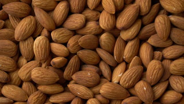 vídeos de stock e filmes b-roll de top view: almonds heap rotating with close up shot - frutos secos