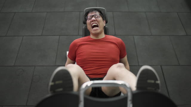 Top View - Asian Large Build man exercising his leg with extremely painful face