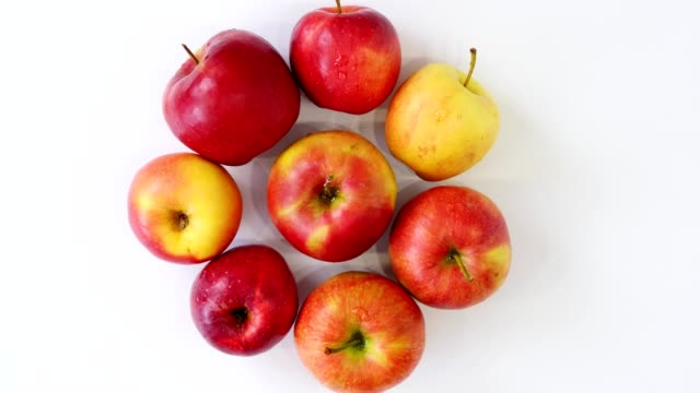 top view, beautiful, red juicy apples laid out in shape of circle, spinning on white background. packaging of fruits, grocery. online shopping. food delivery. apple harvest - vídeo