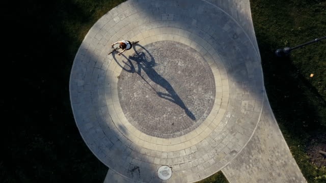 Top view bicycle woman riding a bike on round road in city park Top view bicycle woman riding a bike on round road in city park. Young woman cycling a bike on circle road at city park in summer park. Woman riding bicycle on paved road in city square drone view square composition stock videos & royalty-free footage
