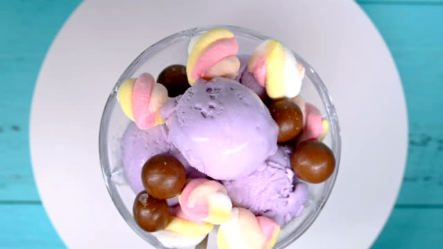 top view bowl of fresh sweet potato flavor ice cream sundae mixed with chocolate candy and marshmallows rotating - vídeo