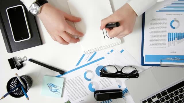 ovanifrån affärsman sitter vid skrivbord skriver plan i anteckningsboken - linjerat papper bakgrund bildbanksvideor och videomaterial från bakom kulisserna