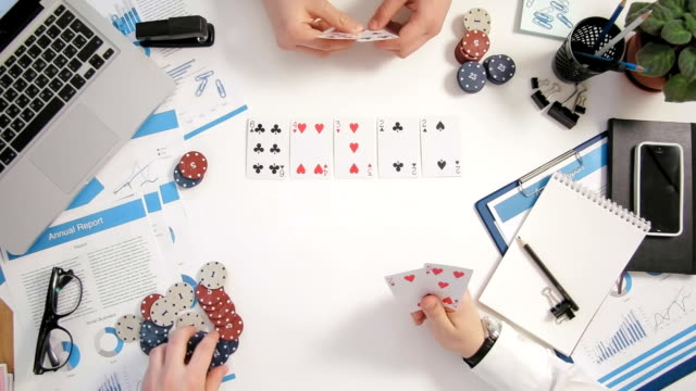 Top view businessmen sitting at office desk and playing poker card