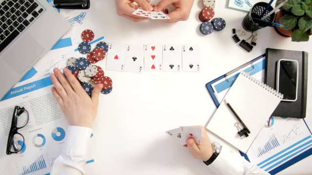 Top view businessmen sitting at office desk playing poker, one goes all in