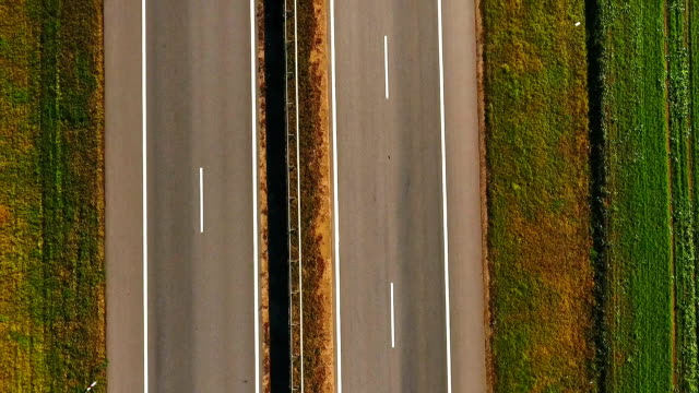 vídeos de stock e filmes b-roll de top view car slowly driving along highway. cars driving on suburban road - reto descrição física