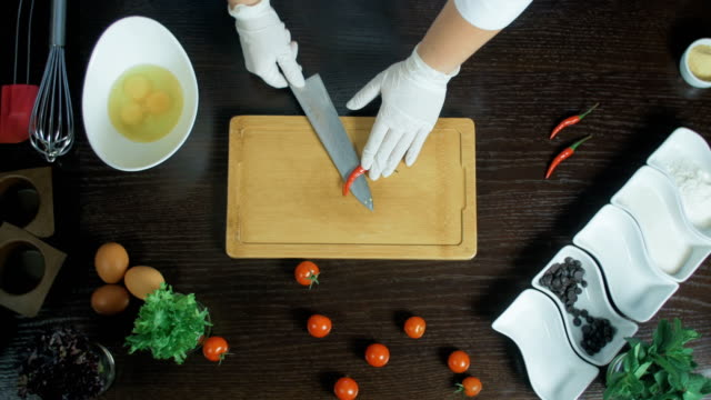 Top view. Chef chopping a carrot with red pepper on cutting board. Remove seeds video