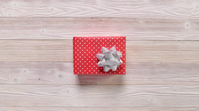 Top view christmas holiday gift boxes on wooden table, stop motion Top view christmas holiday gift boxes on wooden table, stop motion wrapped stock videos & royalty-free footage