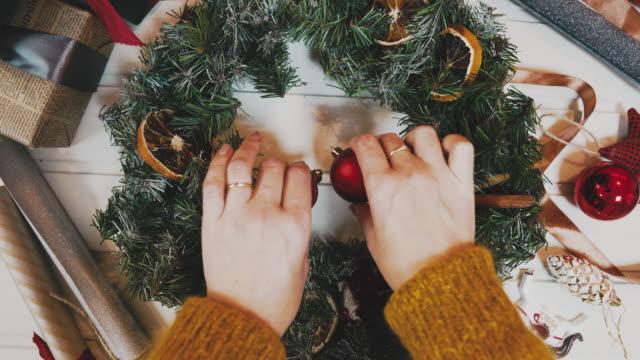 blick auf den weihnachtskranz auf den handwerklichen hintergrund, die hübsche berühmte hand schmücken den weihnachtskranz, die bewegung - advent stock-videos und b-roll-filmmaterial