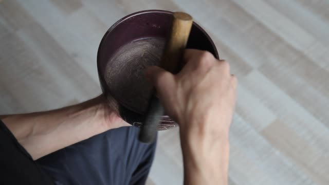 top view close up of a man's hands playing a tibetan singing bowl with a wooden stick