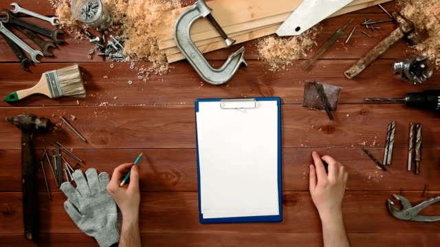 Top view craftsman hands holding a pen and clipboard with paper lying on the table copy space video
