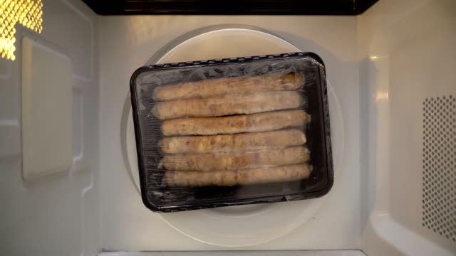 Top view defrosting sausages in microwave Top view defrosting sausages in microwave. Plastic container with breakfast sausage spinning in microwave. frozen stock videos & royalty-free footage